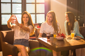 Group of three teenage girls taking a selfie photo for social media while sitting together in a cafe.
