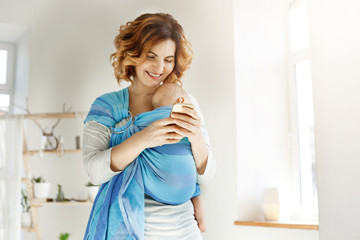Young attractive mother smiles and looking through photos of son on cell phone trying send some pics to her husband. Newborn son sleeping in baby sling. Family concept.