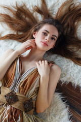 Portrait of a beautiful young girl lying in a room on the floor, top view