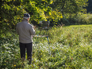 The artist draws a picture in nature. The old man draws a picture.