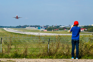 A boy watches a plane's take-off in front of the runway