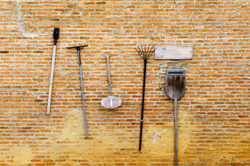 Agricultural or gardening tools hanging on the red brick wall