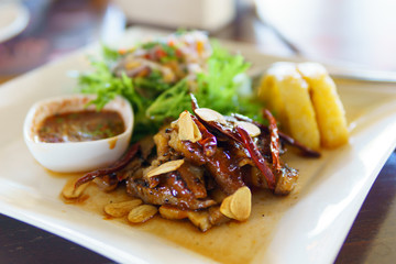 grilled sliced beef with thai local dipping sauce on white dish