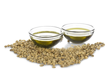 Bowls with hemp oil and seeds on white background