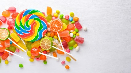 Colored candies, sweets and lollipops. On a white wooden background. Top view. Free space.