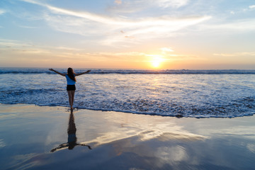 woman open arms under the sunset at the sea with a silhouette reflection. Indian Ocean, Bali, Kuta, low tide