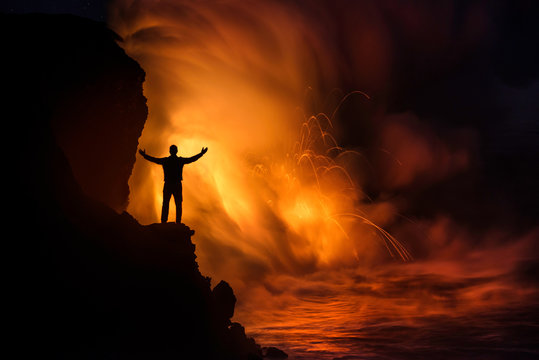 A man standing in front of a lava eruption