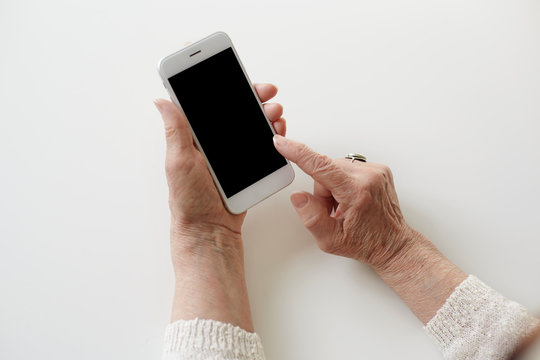 People, technology, job, occupation and age. Close up shot of senior woman hands holding smart phone with copy space. Modern retired elderly female using wifi on mobile, earning money via internet