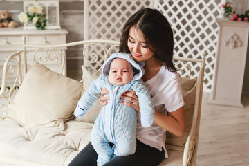 Newborn mixed race baby boy and his young mother. Asian and British new born baby.