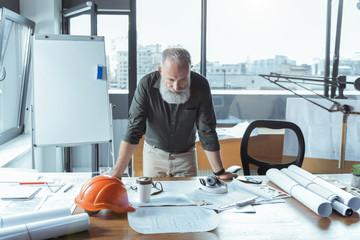Qualified senior engineer is working in office
