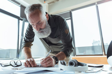 Professional serious worker is laboring on his design plan
