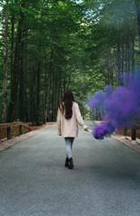 Woman walking with smoke torch