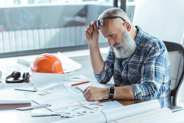 Gray-haired elderly engineer is working with concentration