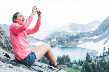 Excited woman sitting high in mountains and taking photo using her smartphone. Risky rock climbing in peaceful wilderness area. Enjoying amazing snowy lake view