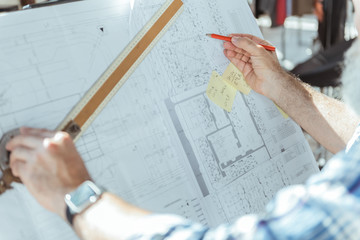 Skillful engineer is working on building plan