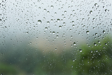 Raindrops on the glass, blurry landscape on background