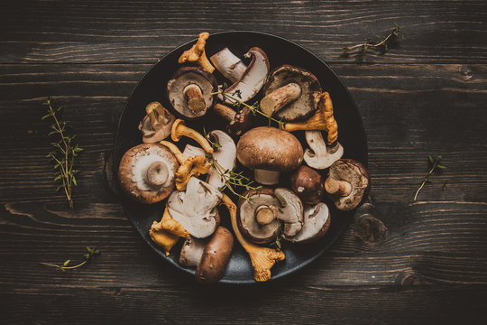 Fresh mixed forest mushrooms on the wooden black table
