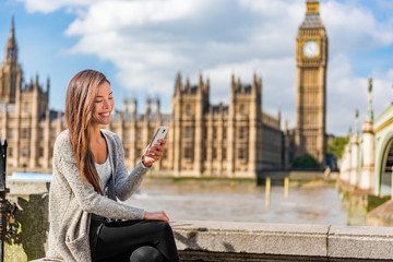 London urban people city lifestyle young Asian woman using mobile phone app texting sms on social media. Happy university student girl holding cellphone at Westminster bridge, Big Ben background.