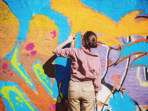 Beautiful Young Girl making a colorful graffiti with aerosol spray on urban street wall. Cinematic toned shot. Creative art. Talented woman in glasses drawing picture.