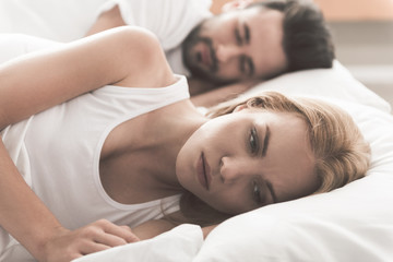 Anxious girl cannot sleep near her husband in bedroom