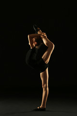 Young girl gymnast on black background