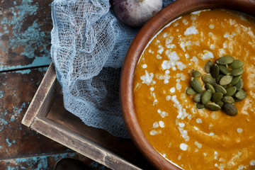 Bowl of traditional homemade pumpkin soup with seads, cream and bread on rustic wooden table