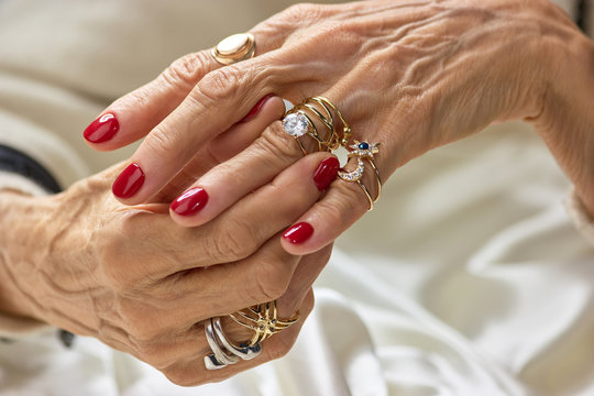 Female hands with golden rings. Senior woman hands with beautiful red nails wearing a lot of golden rings. Womens wealth and beauty.