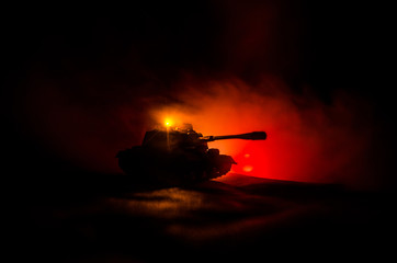 War Concept. Military silhouettes fighting scene on war fog sky background, German tank in action Below Cloudy Skyline At night. Attack scene. Armored vehicles.