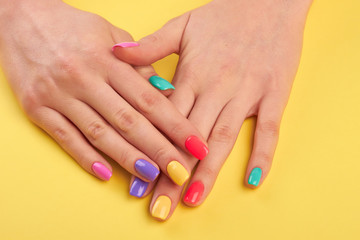 Aluminium Prints Manicure Woman nails painted in different colors. Stylish colorful nails and on a bright background. Nail care studio.