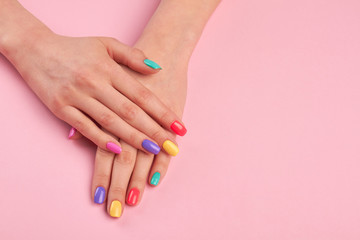 Poster de jardin Manicure Female hands with stylish colorful nails. Beautiful woman hands with pastel colors nails on pink background, copy space.