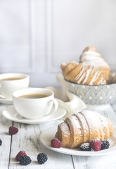 Croissants with fresh berries and two cups of coffee