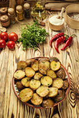 Close up of steaming hot baked potato,Hot buttered jacket baked potatoes,Roasted potato in bowl on wooden table,Oven-baked potatoes with sea salt and rosemary,toasted baked potato strewed with herbs.