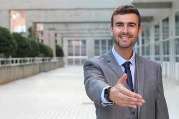 Committed businessman giving a handshake with space for copy