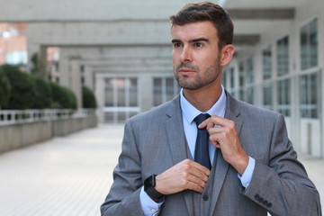 Elegant businessman adjusting his tie