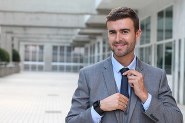 Cocky businessman adjusting his tie with copy space