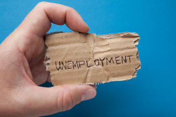 "The word ""unemployment"" written on cardboard in the man's hand, isolated on a blue background, despair."