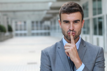 Man using a finger sign to request someone to remain silent