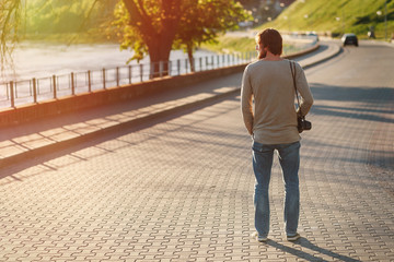 Bearded guy in casual clothes with camera walking down the embankment