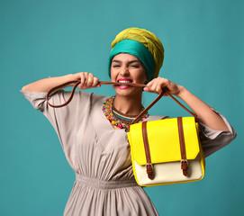 Woman yelling screaming and eating belt of hand hold stylish fashion yellow leather bag handba