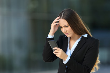 Worried executive reading bad news in a cellphone
