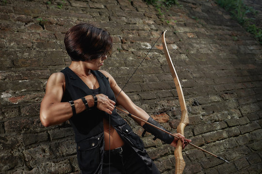 Athletic brunette shooting from bow and tacking focus.