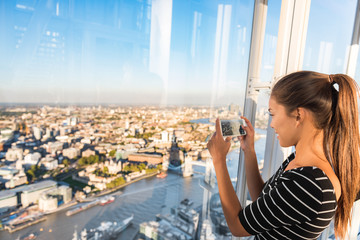 Tourist girl taking phone picture of sunset london skyline view from The Shard. Europe travel tourism.
