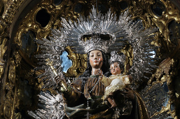 Close-up of traditional procession statue of Madonna and the Child in church of Sevilla, dressed in black, white and silver with some baroque ornaments in behind