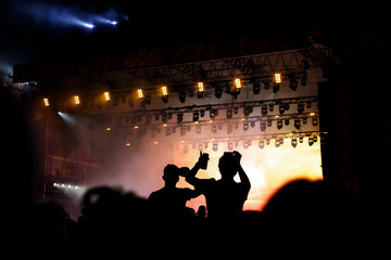 Rock concert, silhouettes of happy people raising up hands.