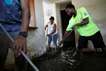 People clean the mud from their flooded house after the area was hit by Hurricane Maria in Toa Baja, Puerto Rico