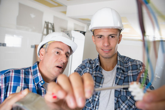 friendly master electrician and apprentice working on breaker panel