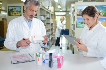 female pharmacist and pharmacy technician posing in drugstore