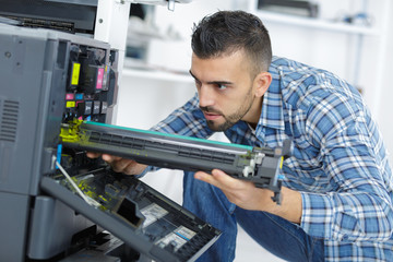 closeup shot young male technician repairing digital photocopier machine