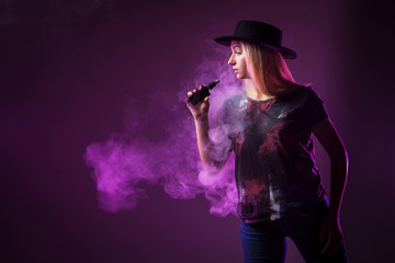 Girl in the smoke of an electronic cigarette. ( vaping ) e-cigarette.