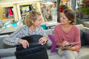 2 women customer and seller discussing price of couch